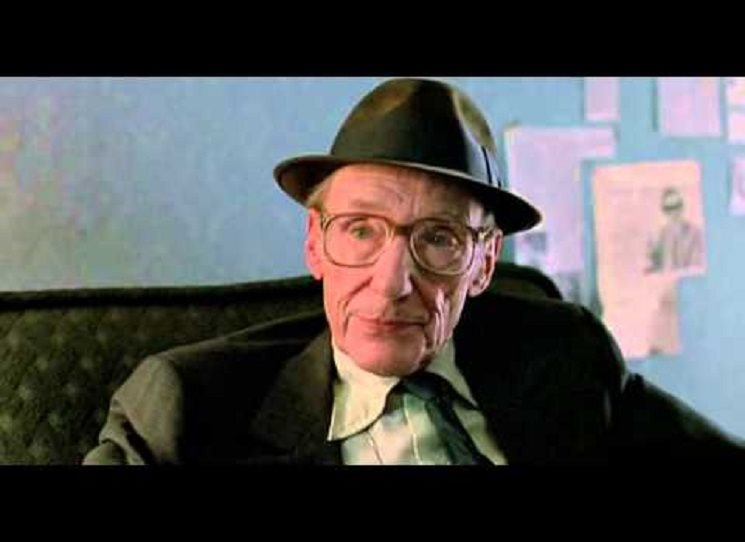 Kůže napjatá na lebce, pěšinka na straně, oblek s vestou a strnulá póza: William S. Burroughs